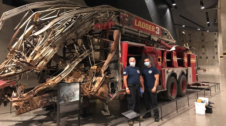 Two firefighters in masks and navy blue T-shirts stand in front of the smashed Ladder 3 firetruck in the 9/11 Memorial Museum.