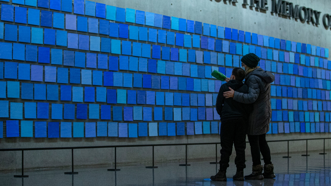 "An older woman wraps her arm around a young boy's shoulder as they look at the inscription ""No Day Shall Erase You From the Memory of Time.""  This quote from Book IX of ""The Aeneid"" by the Roman poet Virgil are are part of a larger art installation by artist Spencer Finch, titled ""Trying to Remember the Color of the Sky on That September Morning."" The words appear amid a sea of blue tiles."