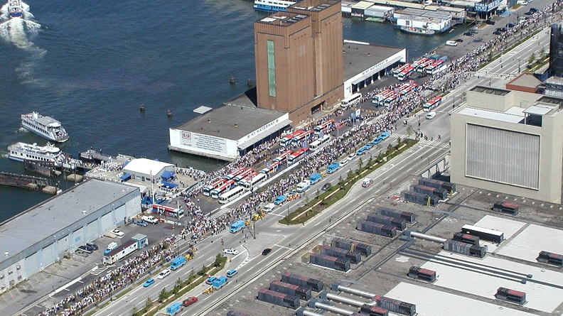 Aerial photograph of the West Midtown Ferry Terminal located at Piers 78 and 79 in Hudson River Park adjacent to the West Side Highway at West 39th Street in Midtown. Large crowds of people are boarding ferries to evacuate lower Manhattan, September 11, 2001.