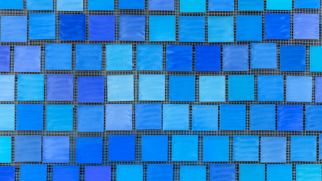 Long alt text: Dozens of square tiles that are varying shades of blue are seen up close in Memorial Hall.