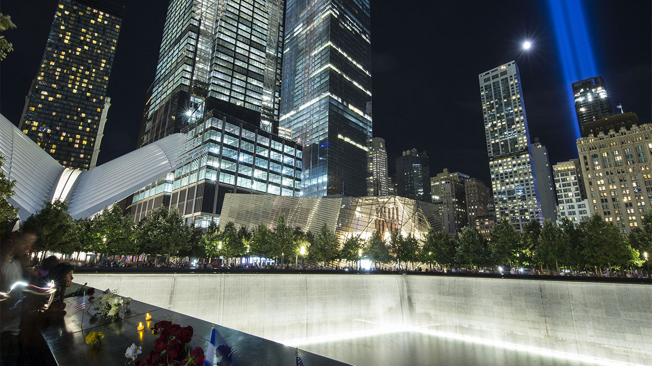 Visitors surround the brightly lit north reflecting pool at night. The Museum pavilion and nearby skyscrapers are also alight. A radiant moon and the blue glow of the Tribute in Light shine above the buildings.