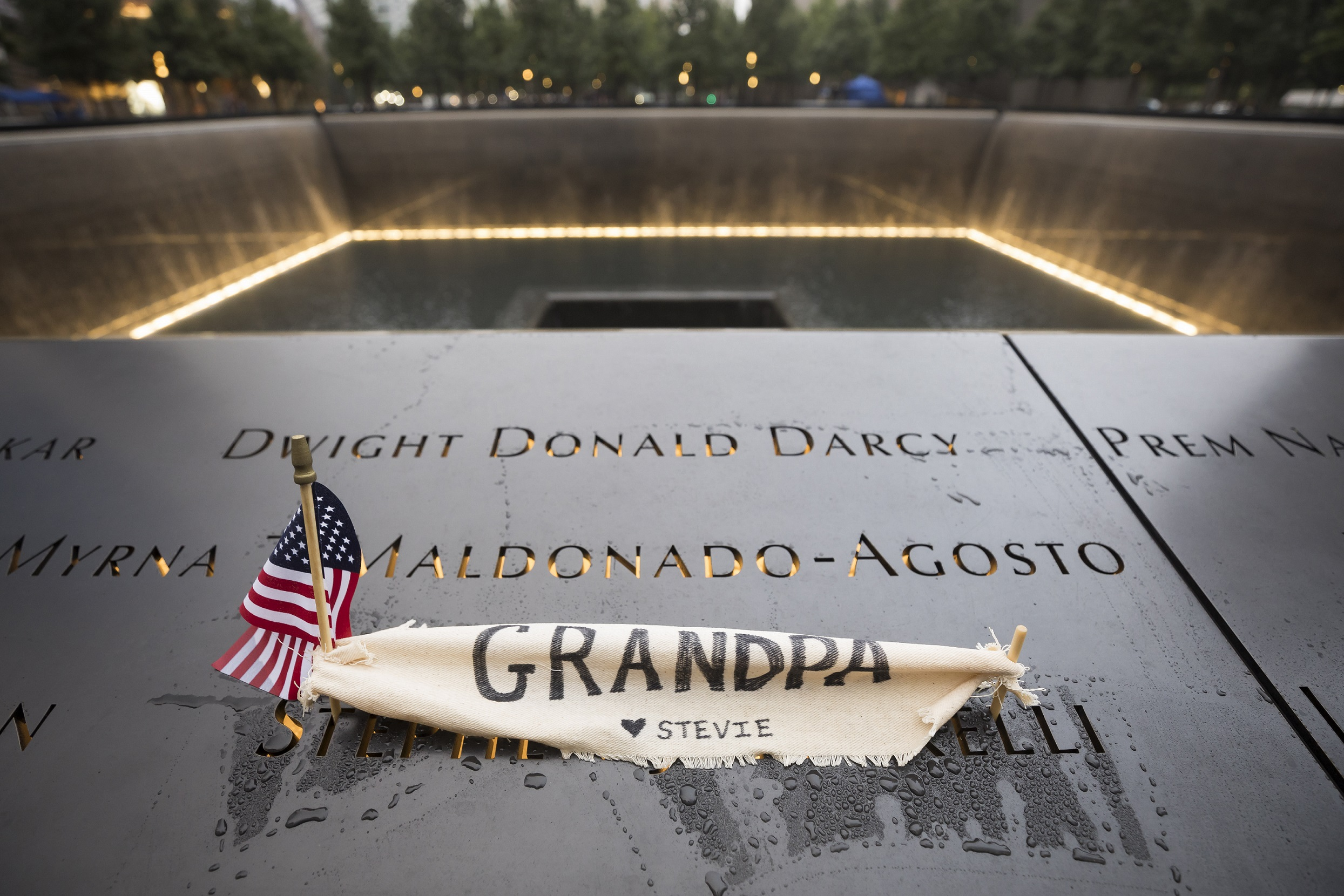 "A small American flag and a hand-written note have been placed at a victim's name on a bronze parapet at the Memorial. The note is written on a piece of cloth and reads ""Grandpa."" Water cascades down a lit reflecting pool in the background."