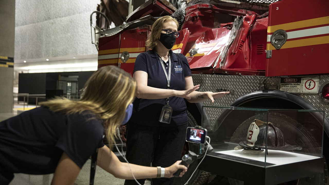 A woman wearing a face mask stands in front of the Ladder 3 firetruck in the Memorial Museum. Another woman films the scene with her smartphone.