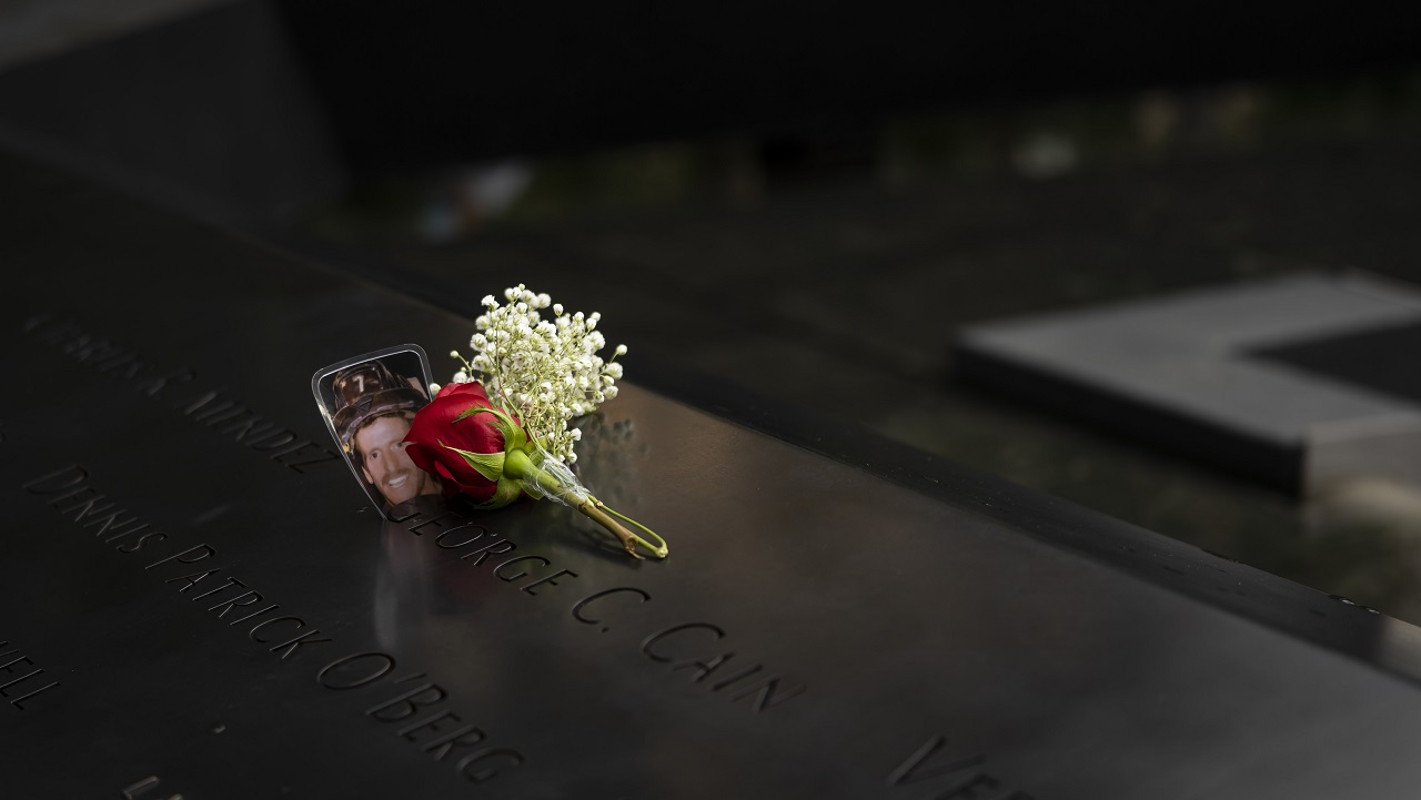 A laminated photo of a firefighter wearing a helmet rests inside a name on the bronze parapet of the Memorial alongside single red rose, surrounded by small white flowers.