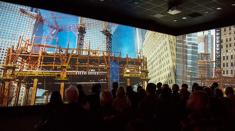 An audience of several dozen people watches a panoramic screen showing rebuilding at the World Trade Center site as part of the Rebirth at Ground Zero exhibition.