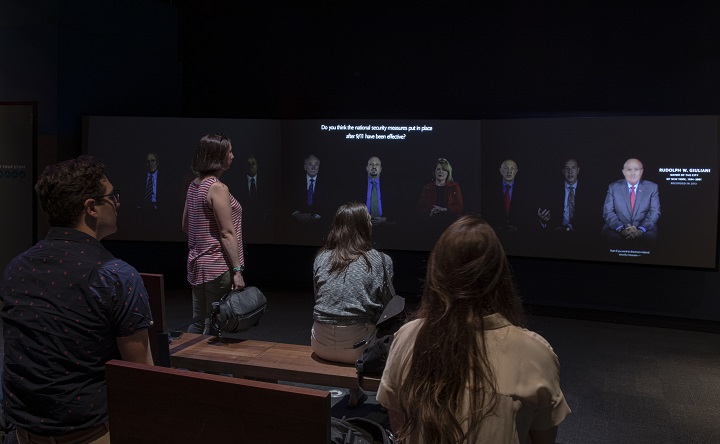 Four visitors watch a video screen that shows survivors recounting their memories of 9/11 in the Reflecting on 9/11 exhibition.  Eight survivors can be seen in a panorama across the long video screen.