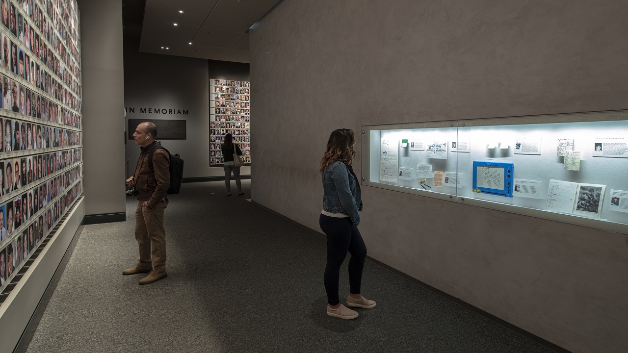 In this interior look at the In Memoriam exhibition, a visitor standing in the foreground is looking at personal items that belonged to victims of the attacks that are on view in a display case.  Two other visitors linger over some of the 2,983 portrait photographs of victims are on walls to the left and right of the chamber.