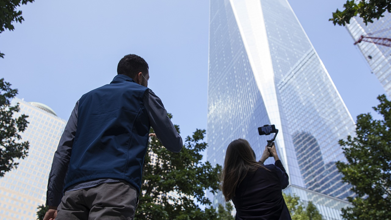 A woman with a smartphone films One World Trade while a tour guide speaks at stands behind her on the 9/11 Memorial plaza.