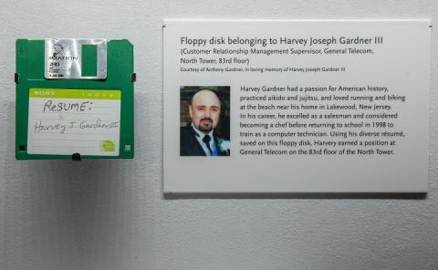 "A green floppy disk marked ""RESUME: Harvey J. Gardner III"" is mounted alongside an exhibition wall label that provides background about the artifact."