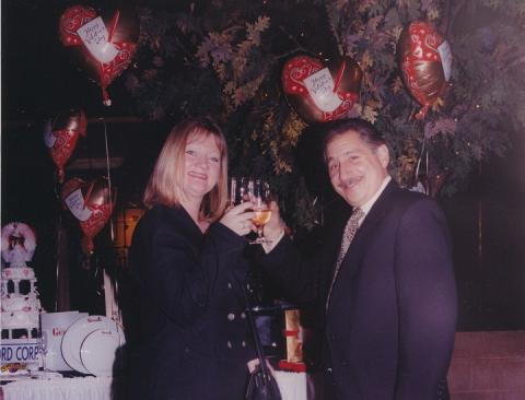 A woman with blonde hair and a man with a mustache toast with champagne in front of a white-tablecloth-covered table and a tree with heart-shaped balloons attached to it.