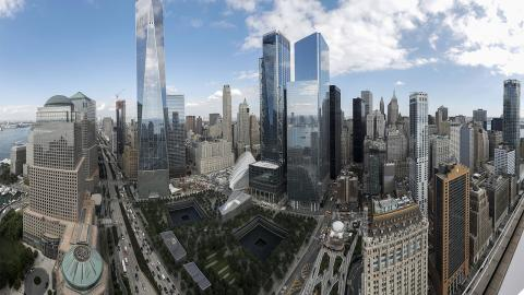 An aerial view over World Trade Center on a partly cloudy day. One World Trade Center towers over the Memorial with the reflecting pools at its center. The skyline of lower Manhattan stands to the right.