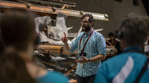 A bearded young male tour guide, standing in front of a mangled segment of an antenna recovered from the World Trade Center, gestures as talks to visitors on a tour of the 9/11 Memorial Museum.