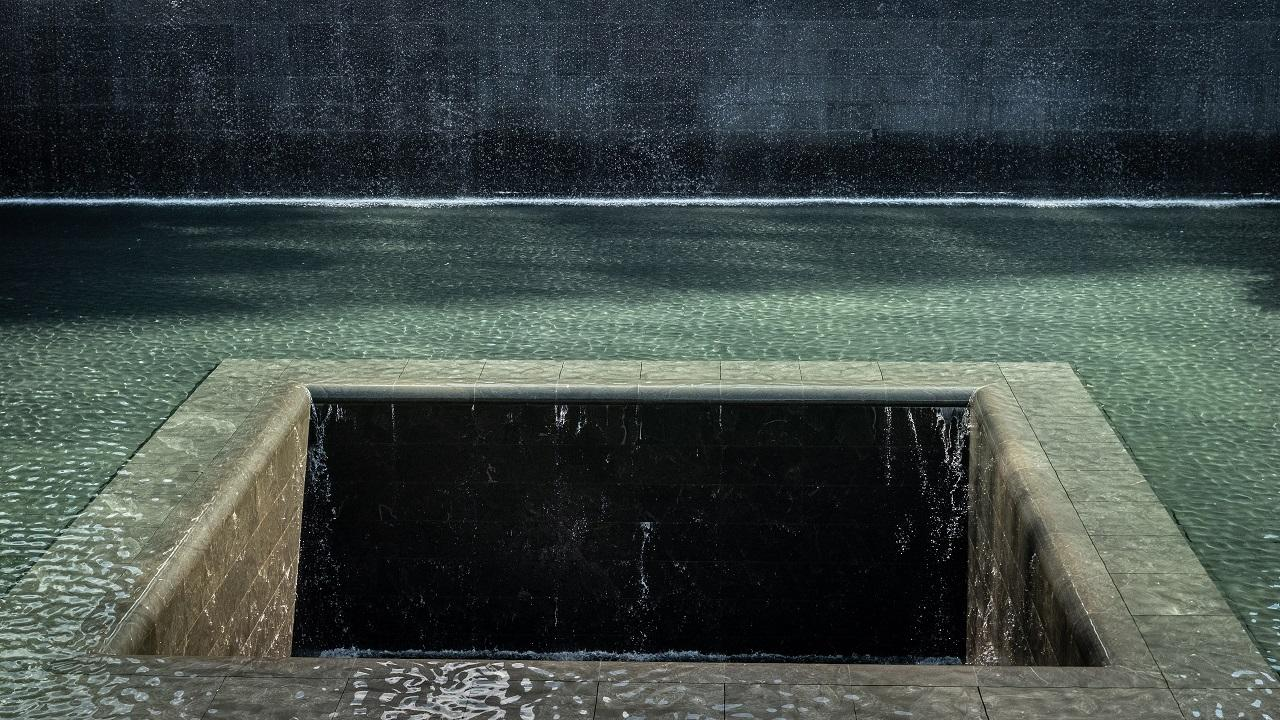 Water flows down four walls and disappears into a void at the center of a Memorial reflecting pool. Sunlight creates shadows on the pooled water.
