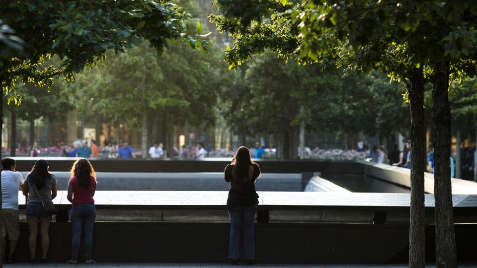 A woman is seen standing at the Memorial parapets at dusk.  She is standing alone with her back to the camera as she takes a photo.