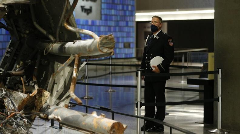 A man in an FDNY uniform looks at the section of television antennae that once sat atop the North Tower of the World Trade Center that is now in the 9/11 Memorial Museum. .
